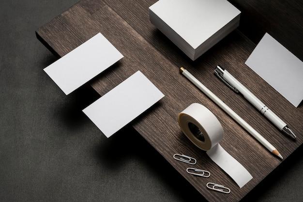 Cartões de visita brancos em branco e acessórios na mesa de madeira