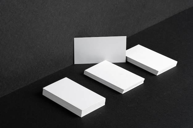 Cartões de visita brancos empilhados para identidade visual na tabela preta