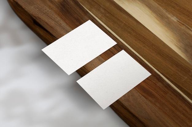 Cartões de visita brancos na superfície de madeira