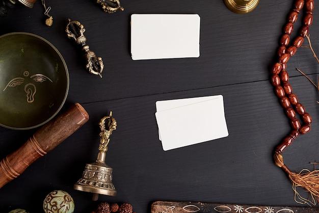 Cartões de visita brancos vazios no meio de objetos religiosos asiáticos