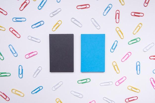 Cartões de visita de papelaria rodeados por clipes de papel