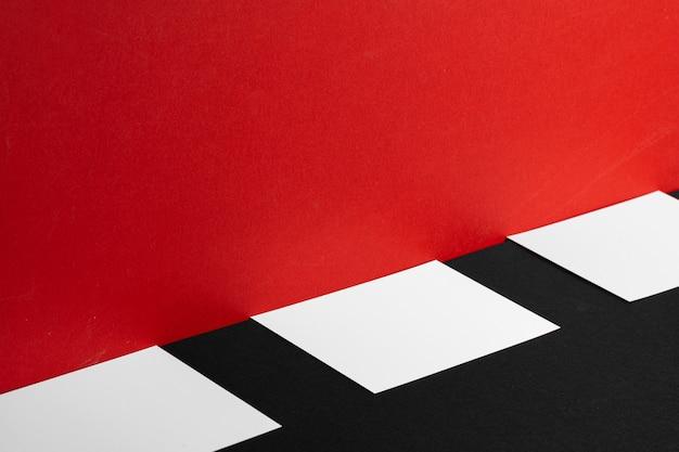 Cartões de visita em branco brancos na mesa vermelha e preta