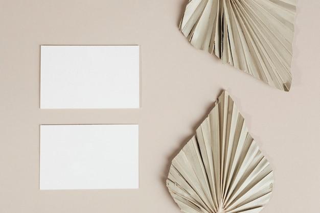 Cartões de visita em branco com folhas de palmeira secas