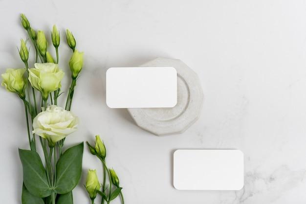 Cartões de visita em branco de maquete para seu projeto, modelo em fundo de mármore cinza com elementos de concreto, flores eustoma. postura plana