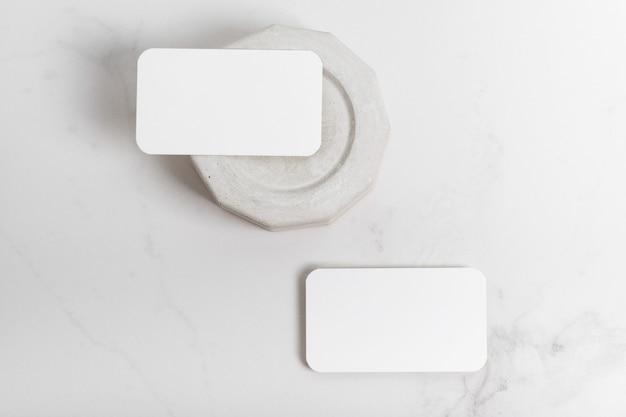 Cartões de visita em branco de maquete para seu projeto, modelo em fundo de mármore cinza com elementos de concreto. postura plana