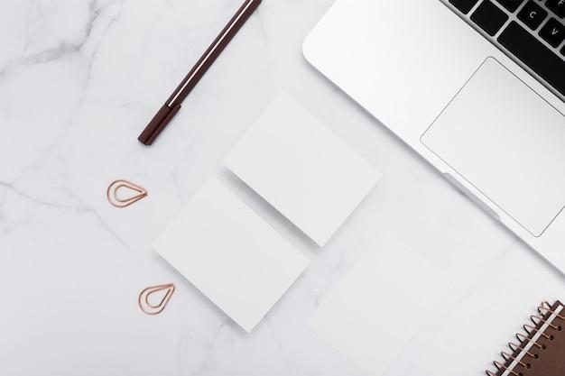 Cartões de visita em branco de papelaria com laptop