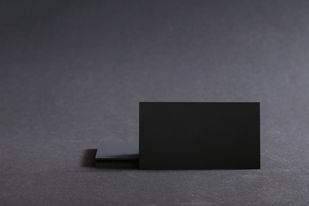 Cartões de visita em branco pretos em uma superfície preta.