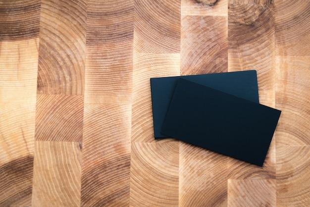 Cartões de visita em branco pretos na superfície de madeira.