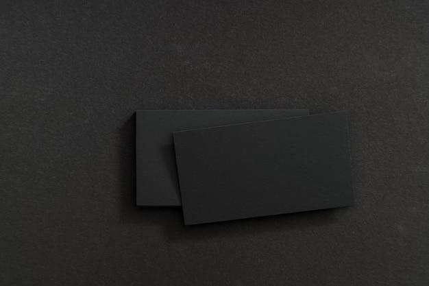 Cartões de visita pretos e em branco em uma mesa preta