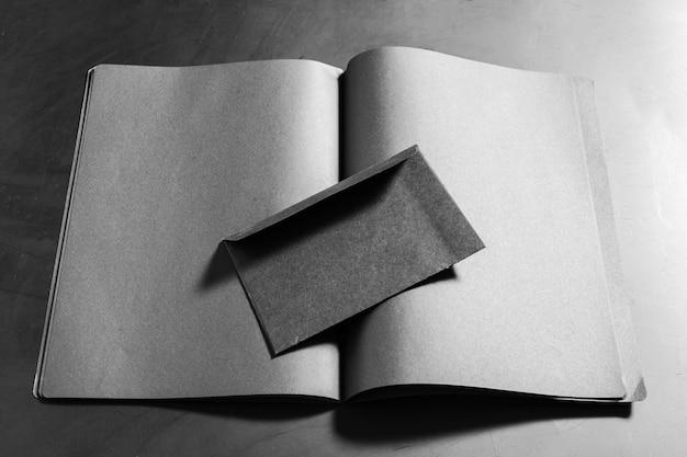 Cartões de visita pretos e livro aberto