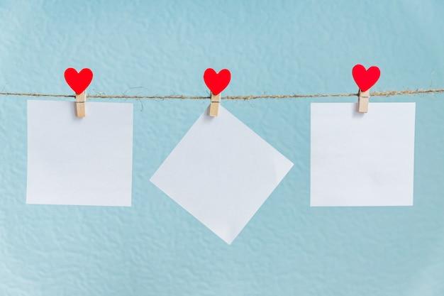 Cartões em branco nos pinos com corações vermelhos. maquete para o texto e o fundo azul para cumprimentos do dia dos namorados
