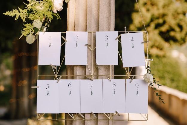 Cartões em branco numerados de planos de assentos em um suporte de vime de metal pendurados em uma inscrição de coluna