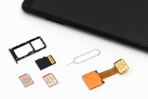 Cartões sim, um cartão de memória, um alfinete perto do smartphone