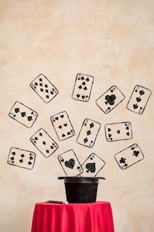 Cartola preta mágica e cartas de jogar na mesa vermelha