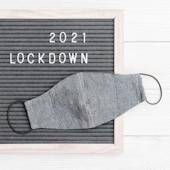 Cartolina flatlay com bloqueio de texto de mensagem 2021 e máscara protetora. bloqueie o conceito de carregamento.