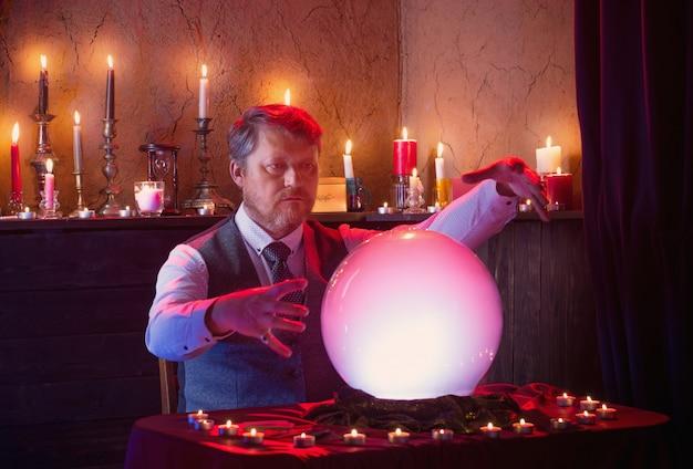 Cartomante de homem com bola de cristal iluminada