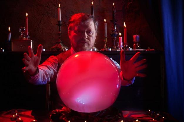 Cartomante masculino com bola de cristal iluminada