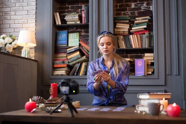 Cartomante profissional. mulher bonita e simpática segurando cartas de tarô enquanto está sentado em frente à câmera
