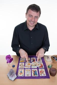 Cartomante usando cartas de tarô na mesa roxa