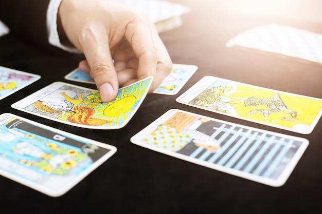 Cartomante usando cartas de tarô na mesa vermelha