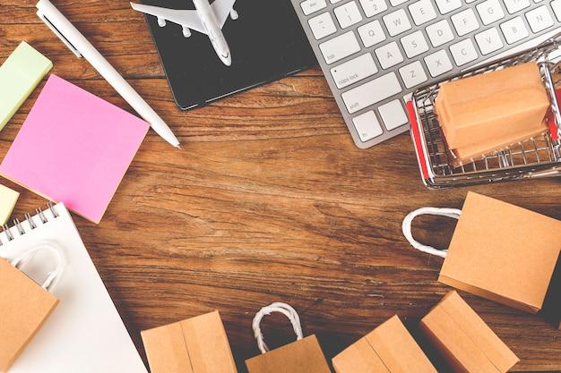 Carton em um carrinho de compras em um teclado de laptop. compras on-line é uma forma de comércio eletrônico que permite aos consumidores comprar diretamente mercadorias de um vendedor pela internet