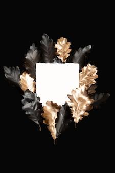 Carvalho preto e dourado pintado à mão deixa moldura em fundo preto. composição de outono luxuosa com cartão de papel branco