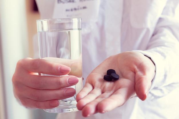 Carvão ativado e água nas mãos de um médico
