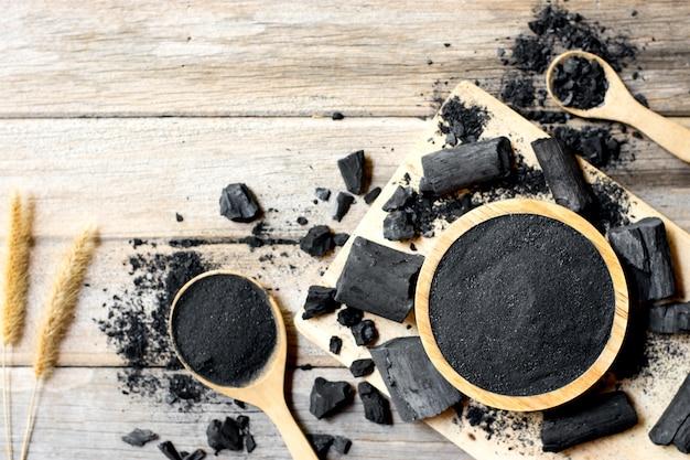 Carvão de madeira em pó, coloque em um copo, colocado sobre uma mesa branca.