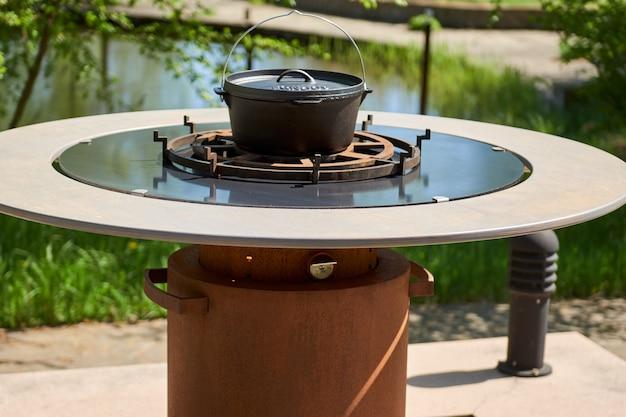 Carvão em chamas no poço da churrasqueira com grade de ferro fundido. superfície de cozinha de mesa redonda. churrasqueira quente com grade de aço inoxidável no quintal grelhados prontos para cozinhar cookout food. grelhe com chamas dentro.