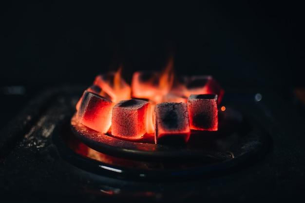 Carvão quente para shisha aquecido no fogão em uma barra de narguilé