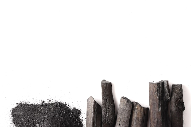 Carvão vegetal e pó (carvão ativado) no fundo branco. espaço livre para o texto