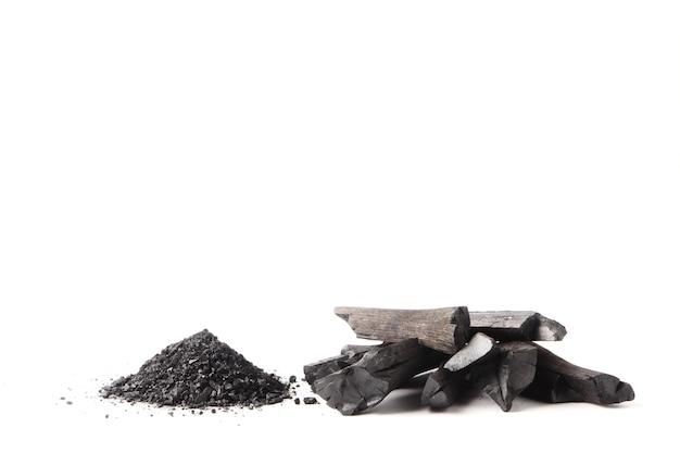 Carvão vegetal e pó (carvão ativado) no fundo branco.