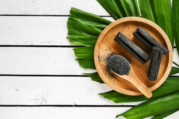 Carvão vegetal e pó de bambu na tabela de madeira. copie o espaço