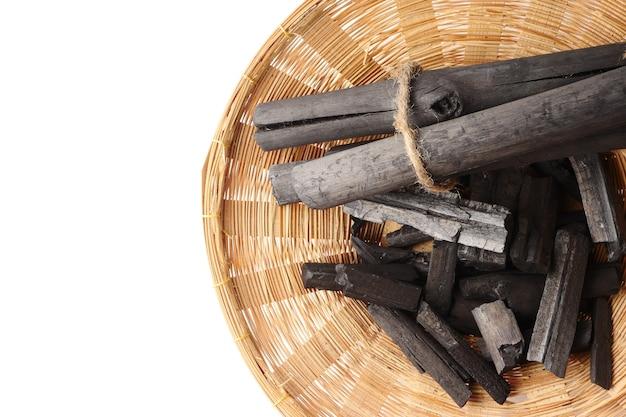 Carvão vegetal na cesta no fundo branco. espaço livre para o texto