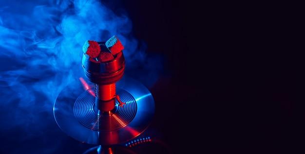 Carvões de shisha encarnados em uma tigela de cachimbo de água de metal contra um fundo de fumaça