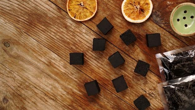 Carvões para narguilé em fundo de madeira com laranjas secas, tabaco e tigela. lugar para texto