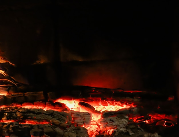 Carvões quentes de madeira queimada na lareira em um espaço de fundo preto para copiar o texto suas palavras