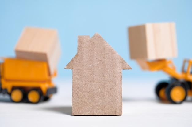 Casa abstrata feita de papelão ao lado da técnica de transporte de materiais.