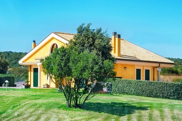 Casa aconchegante com jardim, árvores e gramado verde