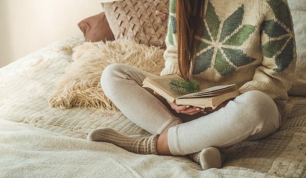Casa aconchegante. mulher bonita está lendo um livro na cama. bom dia com chá e livro. bela jovem relaxante. o conceito de leitura