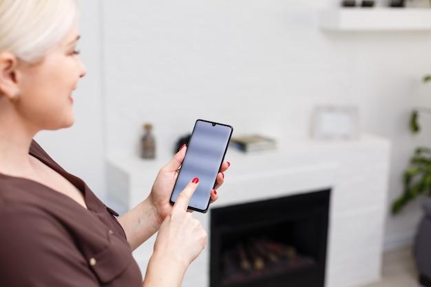 Casa aconchegante. perto da jovem mulher usando smartphone perto da lareira. concentre-se na tela.