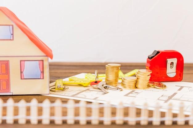Casa além de fita métrica, moedas empilhadas e chave na planta