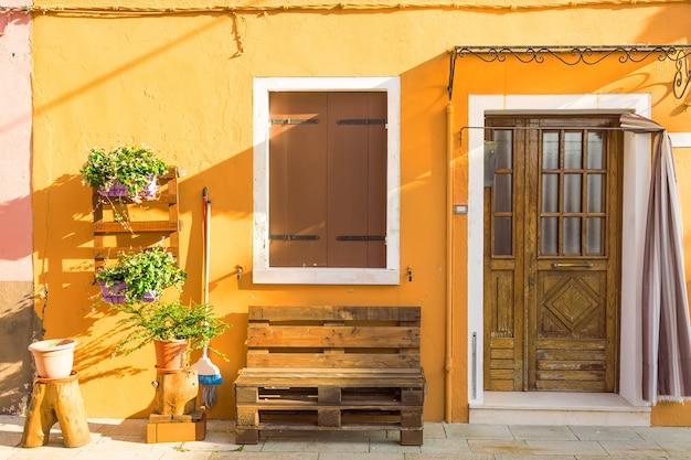 Casa amarela com flores e banco, casas coloridas na ilha de burano, perto de veneza, itália,