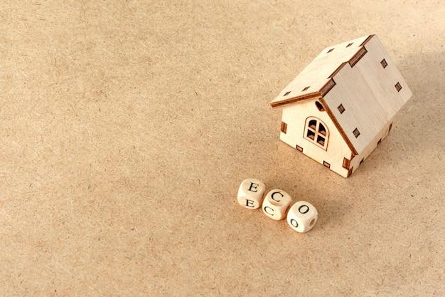 Casa amigável de eco - casa modelo de brinquedo pequeno com a palavra inscrição eco
