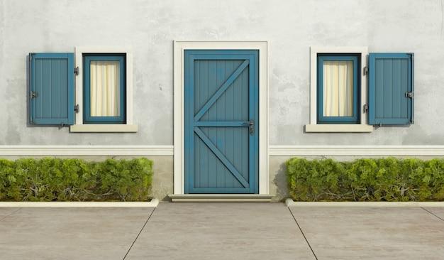 Casa antiga com janela azul e porta da frente