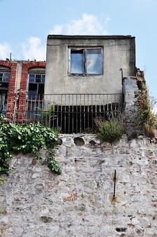 Casa antiga com uma janela. pequena casa em uma grande base de pedra.