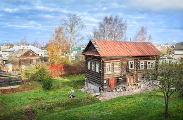 Casa antiga de toras de madeira e pátio entre outros edifícios residenciais em uglich