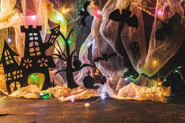 Casa assombrada com uma sepultura e uma árvore assustadora em uma parede de madeira com uma teia de aranha e guirlanda de led