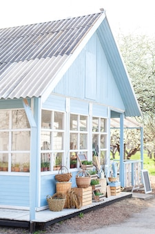 Casa azul acolhedor com um belo jardim em um dia ensolarado. estilo rústico. conceito de outono. casa no país. casa de campo inglesa. quinta bonita com cestas de vime com colheita.