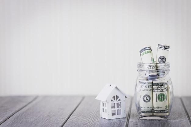 Casa branca com cem dólares no frasco de vidro. investimento imobiliário e hipoteca da casa